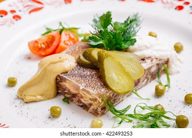 Jellied pork and beef with dill and parsley on the plate on a mustard background