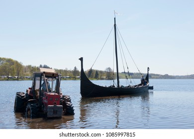 "Jelling, Denmark, May  6, 2018. Replica viking ship. The ship is seaworthy and sails with tourists during the summer. The annual launching is attended by enthusiastic local ""vikings""."