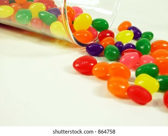 Jelly beans falling out of a glass jar isolated on white.