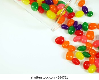 Jelly beans falling out of a glass jar shot from above isolated on white.