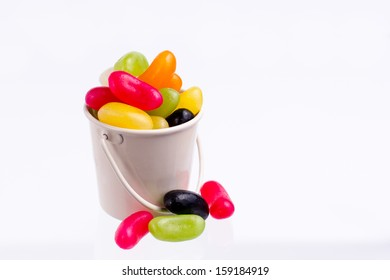 Jelly beans in small bucket on white background