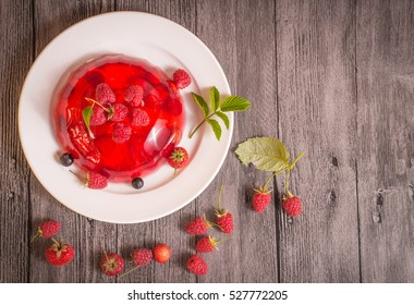 Jelly dessert with strawberries and raspberries on wooden background