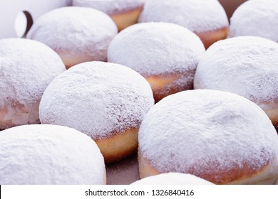 Jelly filled doughnuts with powdered sugar on a white background