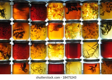 Jelly jars full of preserves sitting on window ledge backlit by sun.