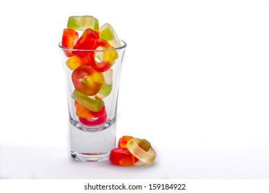 Jelly sweets in shot glass on white background