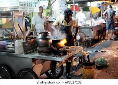 JELUTONG, PENANG, MALAYSIA - JUL 26, 2017: An Indian cook at his Mee Goreng stall in Lorong Batu, Jelutong, Penang. The wet market is the oldest morning market in Penang.