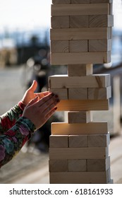 Jenga, girl's hands try to pull out a wooden block, without tipping the tower, group game of physical skill with big blocks for outdoors, vertical