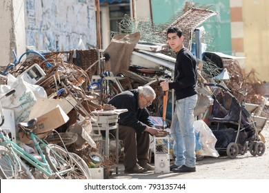 Jenin, Palestine, January 11, 2011: Palestinian man is working with his grandson in a scrap workshop in Jenin refugee camp.