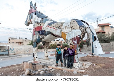 Jenin, Palestine, November 18, 2010: Palestinian children are standing in front of a horse built by German artist from car scrap metal crushed by Israeli tanks in Jenin.