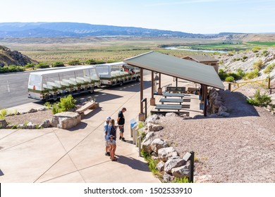 Jensen, USA - July 23, 2019: High angle view of shuttle bus stop, parking lot by Quarry visitor center exhibit hall in Dinosaur National Monument Park with people, Utah