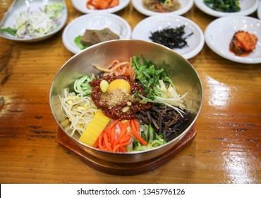 Jeonju Bibimbap with Various Side Dishes on the Wooden Table. Bibimbap is a Traditional Korean Cuisine, Mixed Rice with Meat And Assorted Vegetables.