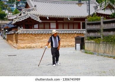JEONJU, SOUTH KOREA - August 24, 2018: old man with a walking stick and a traditional korean house in background, Jeonju city, South Korea