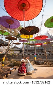 Jeonju, South Korea - January 13 2019: People taking pictures under the colorful umbrellas decorated in a tradition hanok in old town Jeonju.