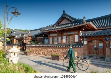 Jeonju, South Korea - September 2018: Tourists in Hanboknam (Korean traditional dress) walking pass ancient house built in Korean traditional architecture in Jeonju Hanok Village