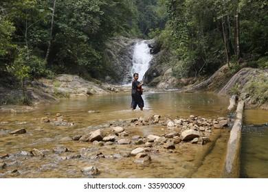 Jerangkang, Pahang, Malaysia-September 19, 2015: A unidentified Malaysian standing in front of a Jerangkang waterfall
