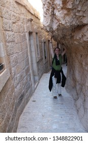 Jericho, Palestine - 4/13/2015: Woman pilgrim touch the big rock in the Orthodox Monastery of Saint George on the Mount of Temptation
