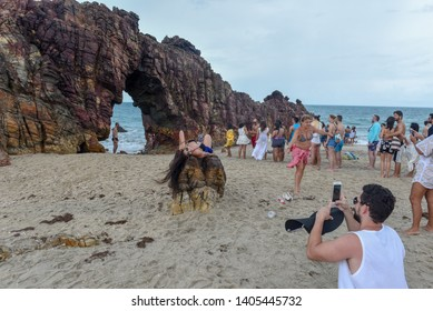 Jericoacoara, Brazil - 9 January 2019: people taking a souvenir photo in front of the natural arch of Jericoacoara on Brazil