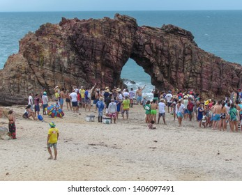 Jericoacoara, Brazil - 9 January 2019: people in line to take a souvenir photo in front of the natural arch of Jericoacoara on Brazil