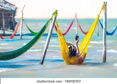 Jericoacoara, Brazil - July 17, 2016: Woman relaxing on hammock taking selfie on vacation