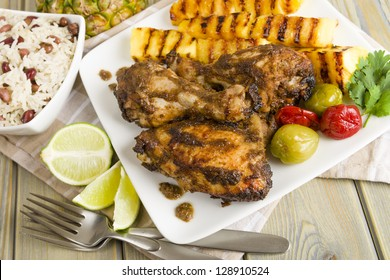 Jerk Chicken - Jamaican marinated BBQ chicken served with grilled pineapple, rice and peas and lime wedges.