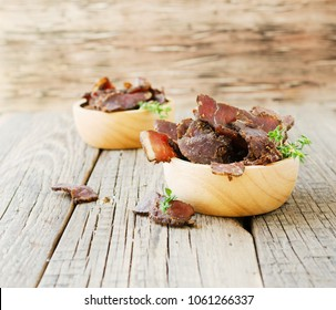 jerked dried meat, cow, deer, wild beast or biltong in wooden bowls on a rustic table, selective focus