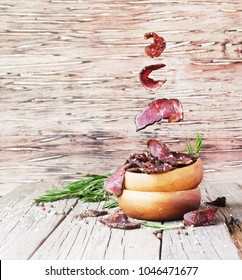 jerked meat, cow, deer, wild beast or biltong in wooden bowls on a rustic table, selective focus