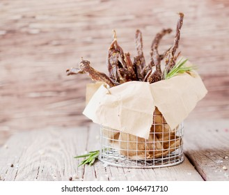 jerked meat, cow, deer, wild beast or biltong in kraft paper bowls on a rustic table, selective focus