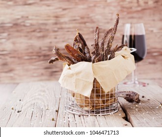 jerked meat, cow, deer, wild beast or biltong with wine bowls on a rustic table, selective focus