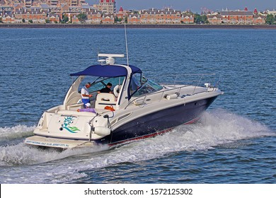 JERSEY CITY, NEW JERSEY - August 22, 2019: A late model Sea Ray 360 Sundancer on the New Jersey side of the Hudson River. A 360 Sundancer is the entry point into Sea Ray's Sport Yacht class of boats.