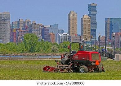 JERSEY CITY, NEW JERSEY - MAY 22, 2019: A Toro Groundmaster 5900 ride-on lawnmower with a number of skyscrapers visible in the background. This mower is loaded with productivity-boosting advantages.