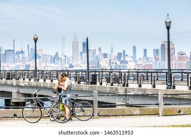Jersey City, NJ / USA - Jun 2019: Manhattan skyline form Liberty State Park, Cyclists stay near bridge.