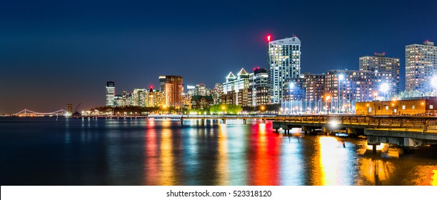 Jersey City skyline panorama by night, reflected in Hudson River, with Verrazano Narrows Bridge in the background