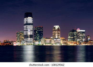 Jersey City skyline with skyscrapers at night over Hudson River viewed from New York City Manhattan downtown.