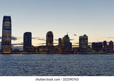 Jersey City skyline with skyscrapers at night over Hudson River viewed from New York City Manhattan downtown