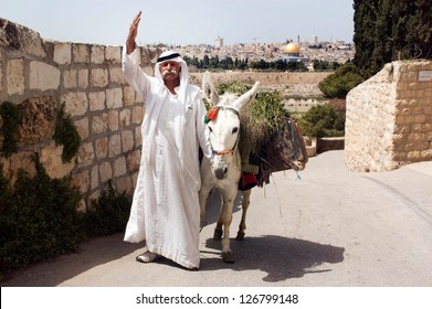 JERUSALEM - APRIL 13:Arab man and white donkey wave to peace against the Temple Mount on April 04 2006 in Jerusalem, Israel.It's the most disputed holy ground between Muslims and Jewish people.