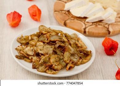 Jerusalem artichoke chips on wooden background