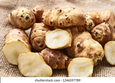 Jerusalem artichoke or sunchoke on sackcloth background. Healthy and benefits of sunroot.