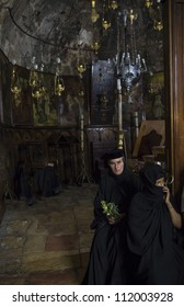 JERUSALEM - AUGUST 25 : Unidentified nuns prays in the Tomb of Mary in Gethsemane during the feast of the Assumption of the Virgin Mary on August 25 2012 in old Jerusalem Israel