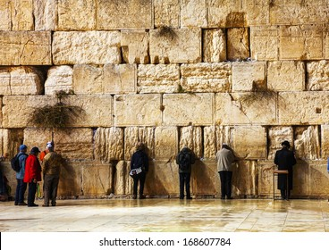 JERUSALEM - DECEMBER 15: The Western Wall with a praying pilgrims on December 15, 2013 in Jerusalem. It's located in the Old City of Jerusalem at the foot of the western side of the Temple Mount.