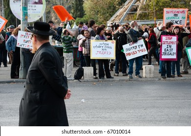 JERUSALEM - DECEMBER 3: A Jewish man passes activists demonstrating in the Sheikh Jarrah neighborhood of East Jerusalem on Dec. 3, 2010 to protest the takeover of Palestinian homes by Jewish settlers.