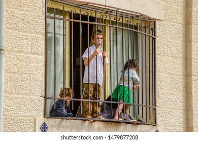 Jerusalem, Isaril. 05.04.2018. Jewish children in the window behind bars. The boy with the pacifier is pressed against the grate by his face and looks plaintively.