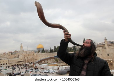 Jerusalem / Israel- 01.24.2018: A bearded Jewish man trumpets into a shofar - a Jewish ritual brass musical instrument at the background of the Wailing Wall and old city of Jerusalem.