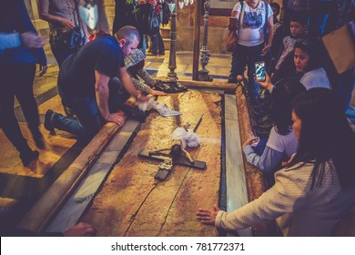 Jerusalem, Israel - 02 Oct, 2017: Prayers touching stone of Anointing in the Holy Sepulcher Church in Jerusalem. Church and Empty Tomb are the most sacred places for all Christians people in the world