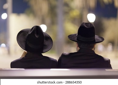JERUSALEM, ISRAEL - 02 OCTOBER 2012: The silhouette of two Jewish men sitting on the bench. Late evening. Jerusalem city, Israel.