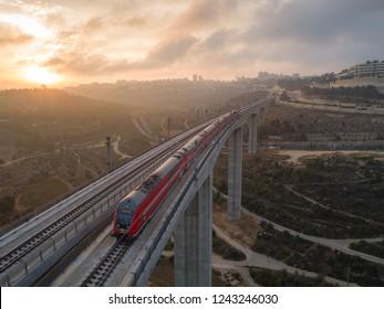 Jerusalem, Israel - 10-17-2018: The fast train connecting Jerusalem to Tel-Aviv, crossing over a valley bridge at dawn.