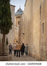 Jerusalem, Israel - 16 December, 2018: Tourists walking through a an alley on mount Zion towards Dormition Abbey.