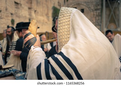 Jerusalem, Israel - 23 August, 2018: A Jewish worshipper blows the Shofar during morning prayers at the Western Wall