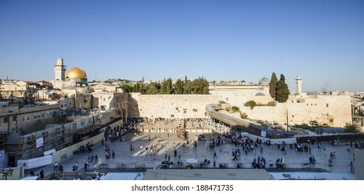 JERUSALEM, ISRAEL - APRIL 18, 2014: The Western Wall crowded with Passover prayers, and the El-Aksa Mosque and the Dome of the Rock in the background, in the old city of Jerusalem, Israel