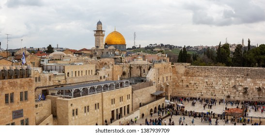 Jerusalem, Israel - April 2, 2019: Aerial panoramic view from above of the crowds of people at the Western Wall in the Old City during a cloudy day.