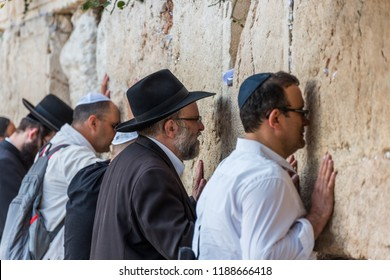 Jerusalem, Israel, Aug 19th, 2018: Othodox jewish men wailing at Western Wall, Wailing Wall, an ancient limestone wall in the Old City of Jerusalem, part of the expansion of the Second Jewish Temple